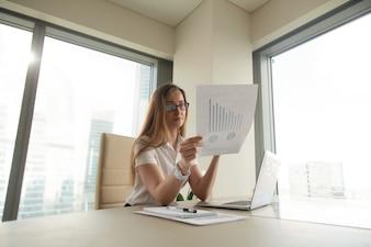 Bizneswomanu czytania dokument z wykresami
