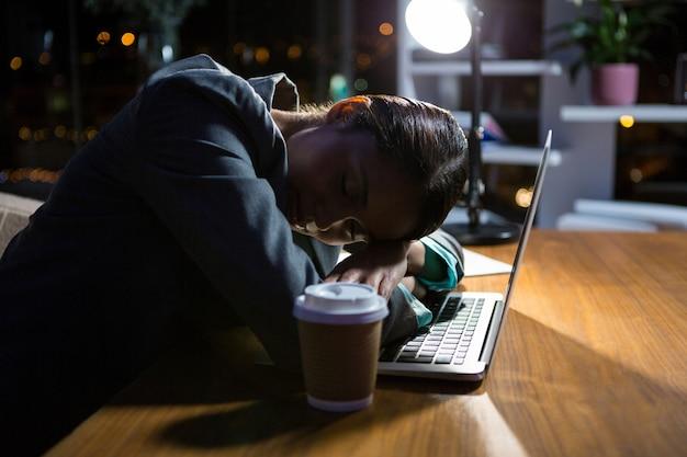 Bizneswomanu dosypianie podczas gdy pracujący w biurze