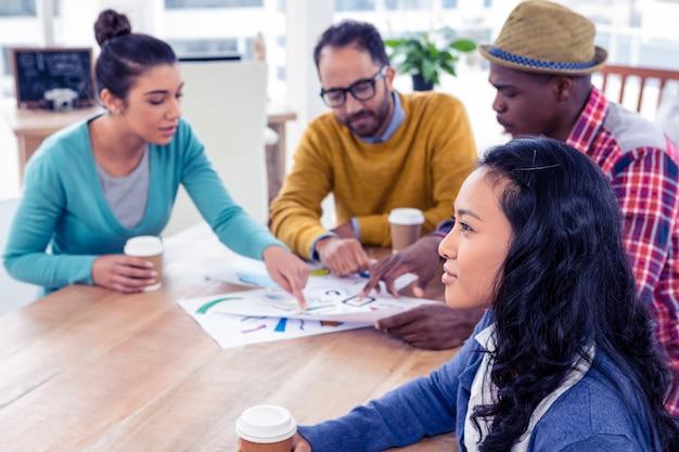 Bizneswomanu dzień marzy z kolegami dyskutuje przy kreatywnie biurem