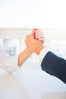 Bizneswomanu i biznesmena zapaśnictwa ręki na biurku