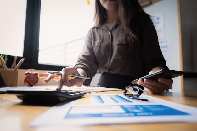 Bizneswomanu lub księgowego ręki trzyma smartphone z kalkulatorem