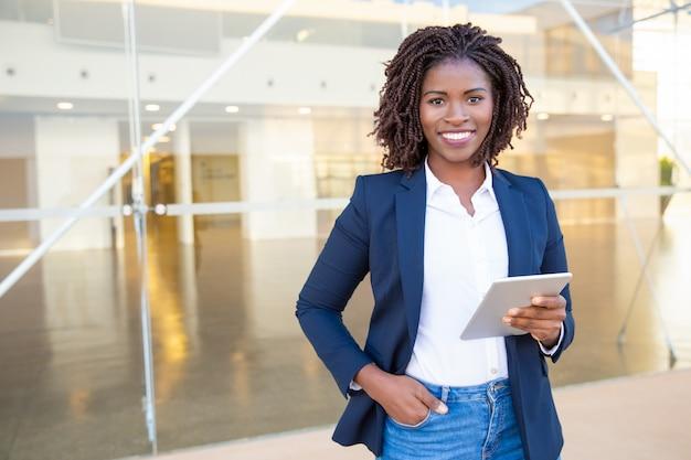 Bizneswomanu mienia pastylki komputer osobisty i ono uśmiecha się przy kamerą
