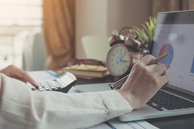 Bizneswomanu mienia pióro i wskaż arkusz danych podczas korzystania z laptopa i kalkulatora
