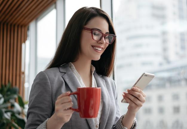 Bizneswomanu mienia telefon komórkowy, filiżanka kawy, komunikacja, robi zakupy online