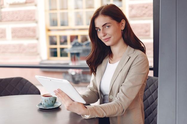 Bizneswomanu obsiadanie przy stołem z pastylką