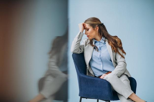 Bizneswomanu obsiadanie w krześle przy biurem
