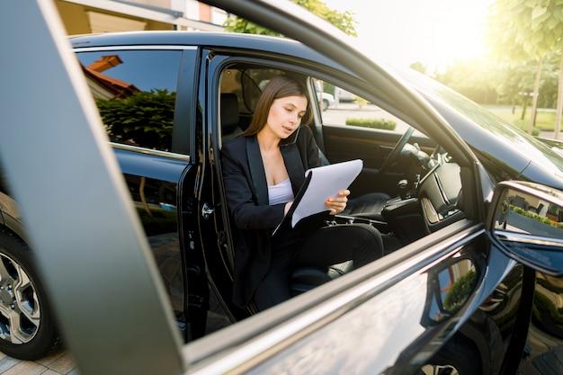 Bizneswomanu obsiadanie w samochodzie z notatnikiem opowiada na telefonie komórkowym i robi notatkom na papierze. wykonawczy kobieta pracuje w luksusowym samochodzie.