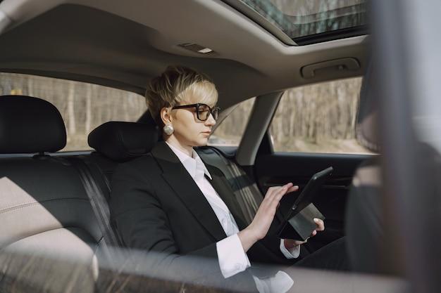 Bizneswomanu obsiadanie wśrodku samochodu i używa pastylkę