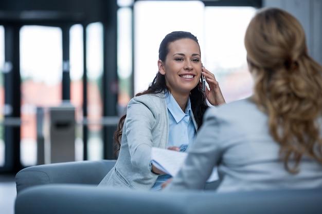 Bizneswomanu obsiadanie z kolegą i opowiadać na telefonie komórkowym