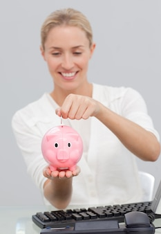 Bizneswomanu oszczędzania pieniądze w piggibank