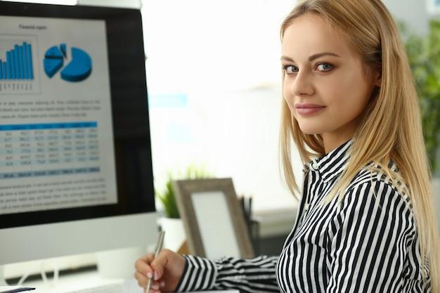 Bizneswomanu portret siedzi przy stołem z desktop