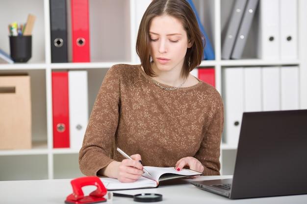 Bizneswomanu portret w biurze używać laptop i robić notatkom