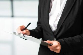 Bizneswomanu writing na schowku z czarnym piórem