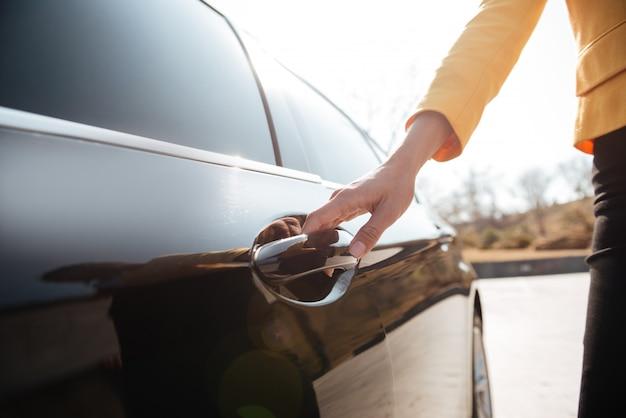 Bizneswomany otwiera drzwi czarny samochód