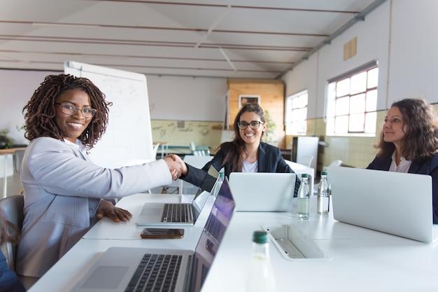 Bizneswomany trząść ręki i ono uśmiecha się przy kamerą