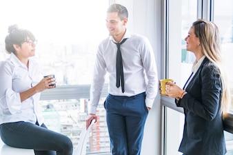 Bizneswomany trzyma filiżankę opowiada z biznesmenem