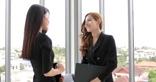 Bizneswomany używa notatnika i pastylki dla dyskutować dokumenty i pomysły w spotkaniu