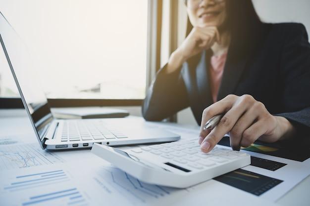 Bizneswomen księgowy używa kalkulatora i laptopa do prowadzenia rachunku