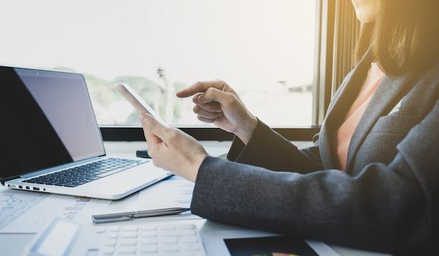 Bizneswomen księgowy używa smartfona i laptopa do prowadzenia rachunku