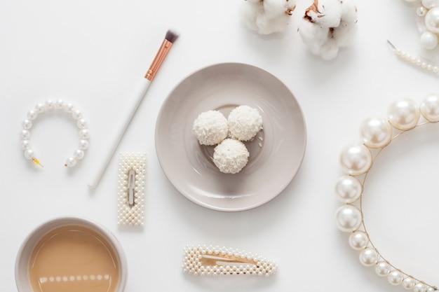 Biżuteria dla panny młodej, perły, pędzle do makijażu, delikatne kolory, cukierki i kawa, na białej przestrzeni