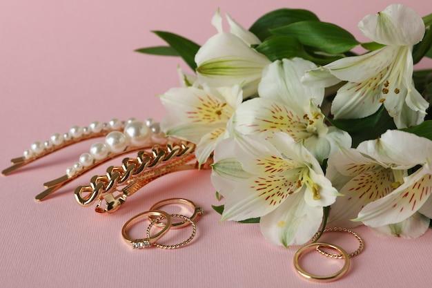 Biżuteria i kwiaty na różowym tle, z bliska