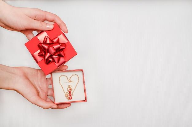 Biżuteria jako prezent na walentynki. wyprzedaż świąteczna. złoty łańcuszek z czerwonymi kamieniami w kształcie serca w pudełku w rękach kobiety na białym stole. dla sklepów jubilerskich.