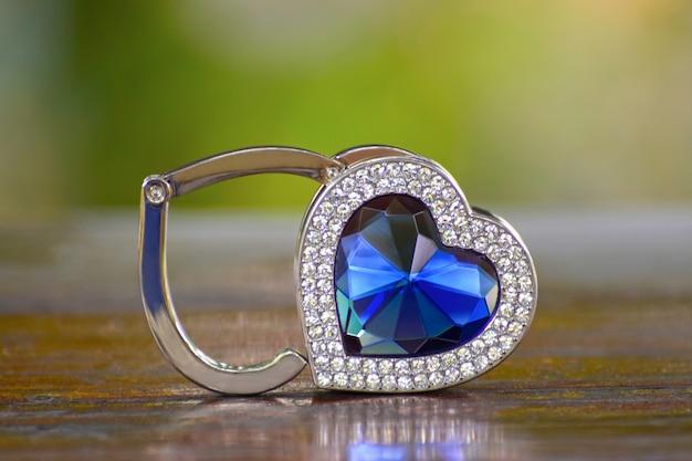 Biżuteria jest wisiorek z białego złota. ozdobiony niebieskimi kamieniami osadzonymi na drewnianej podłodze