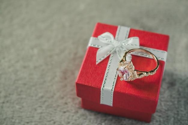 Biżuteria różowy pierścionek z brylantem na czerwonym pudełku