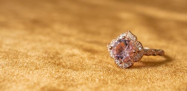 Biżuteria różowy pierścionek z brylantem na tle złotej tkaniny z bliska