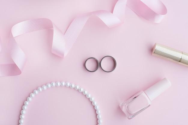 Biżuteria ślubna dzwoni w składzie na różowym tle