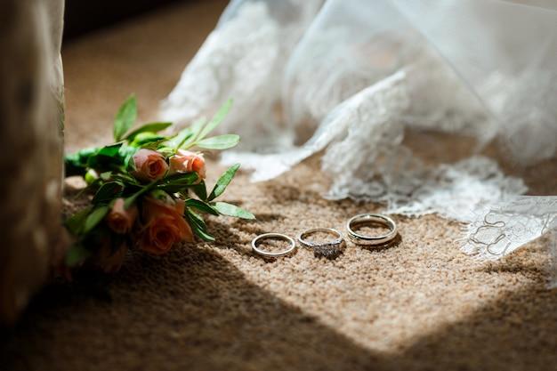 Biżuteria ślubna leżąca w pobliżu welonu z koronką i kwiatami