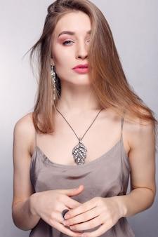 Biżuteria, wakacje, luksus i koncepcja ludzi - piękna kobieca twarz z naturalną idealną skórą. złota skóra kobiety. złote kolczyki, pierścionek i naszyjnik. kosmetyki, uroda i manicure na paznokcie