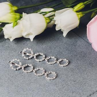 Biżuteria wykonana ze srebra i białego kamienia. agatowe bransoletki, srebrne pierścionki i kolczyki na lekkiej powierzchni, widok z góry, leżał płasko, kopia przestrzeń. biżuteria damska na szarej powierzchni z wolnym miejscem na tekst.