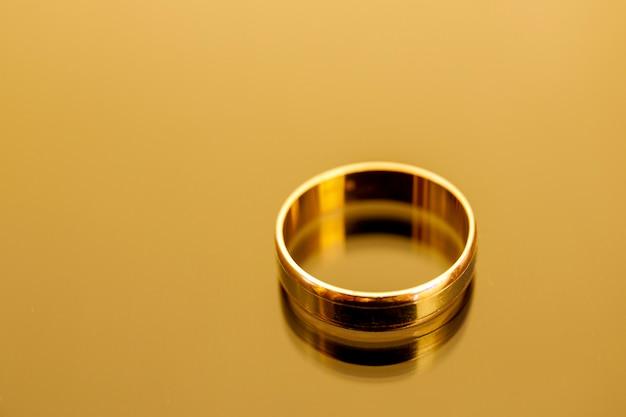 Biżuteria złoty pierścionek odizolowywający na żółtym tle