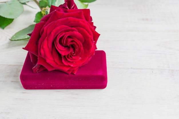Biżuterii prezenta pudełko i bautiful czerwieni róża na drewnianym tle.