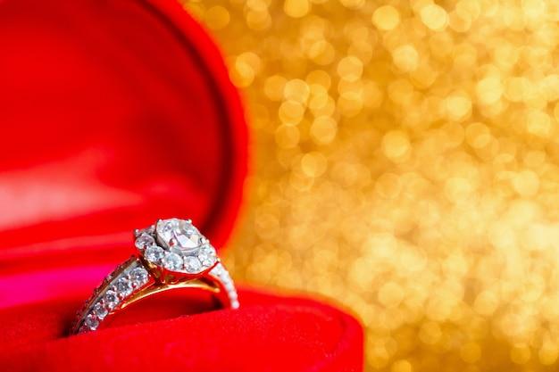 Biżuteryjny pierścionek z brylantem w pudełku prezentowym z abstrakcyjnym świątecznym brokatem