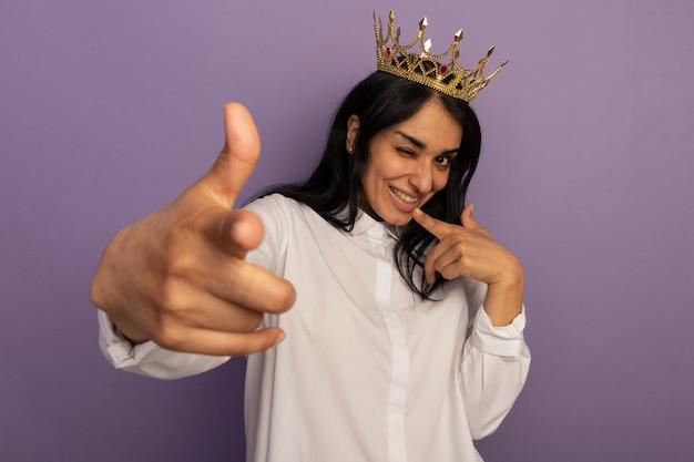 Bkinked młoda piękna dziewczyna ubrana w białą koszulkę i koronę, pokazując gest odizolowany na fioletowo