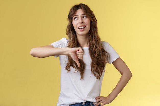 Bla bla nudne. niewzruszona apatyczna snobistyczna atrakcyjna kędzierzawa dziewczyna odwraca wzrok ekspresowa pogarda pogarda pokazuje kciuk w dół marszcząc brwi dzieląc się negatywną oceną złą opinią żółte tło