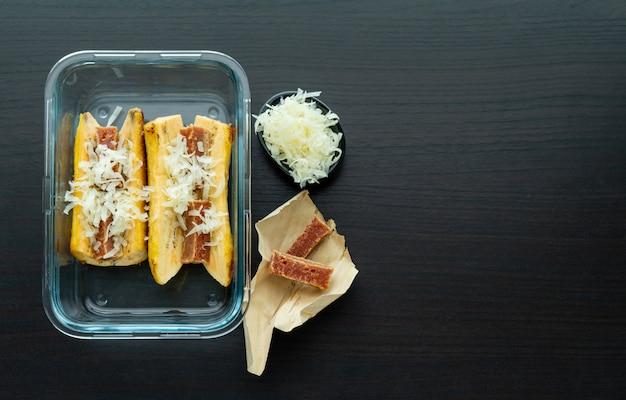 Blacha do pieczenia dojrzałych bananów z guawą i kanapką z serem na czarnej drewnianej podstawie. typowa koncepcja kolumbijskiej żywności. skopiuj miejsce
