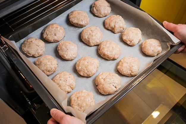 Blacha do pieczenia z kotletami włożonymi do piekarnika. koncepcja domowego jedzenia, gotowanie.