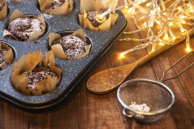 Blacha do pieczenia ze smacznymi babeczkami czekoladowymi na drewnianym stole
