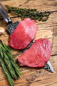 Black angus surowego mięsa wołowego stek z polędwicy na nóż rzeźnika. drewniane tła. widok z góry.