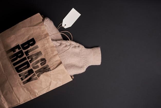 Black friday concept ciepły sweter z dzianiny w torbie na zakupy zimowe ubrania zakupione w czarnym fr...