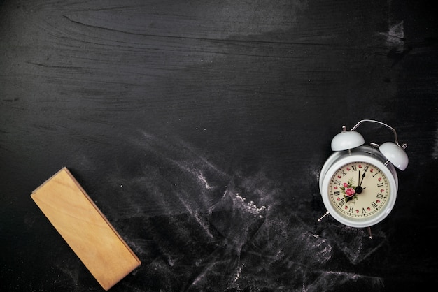 Blackboard gumka z białym budzikiem na blackboard dla tła, chalkboard tekstura dla edukaci.
