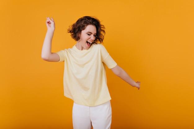 Blada brązowowłosa dziewczyna w żółtej koszulce tańczy z natchnionym wyrazem twarzy. aktywna młoda kobieta w strój dorywczo lato, zabawy w pomieszczeniach.