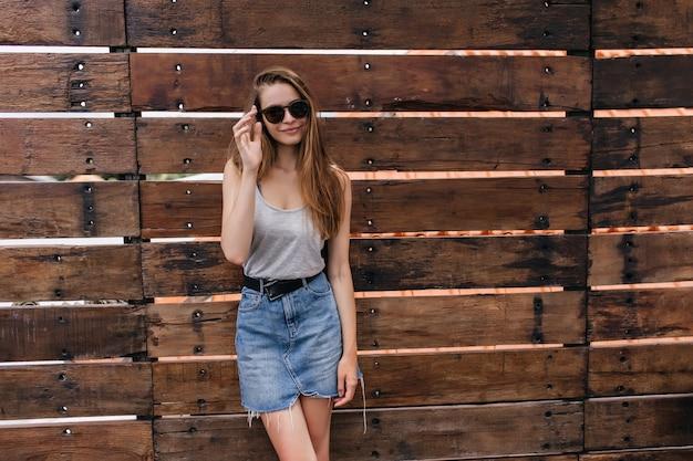 Blada fascynująca dziewczyna w okularach przeciwsłonecznych stojących na drewnianej ścianie. radosna biała modelka w dżinsowej spódnicy relaksująca.