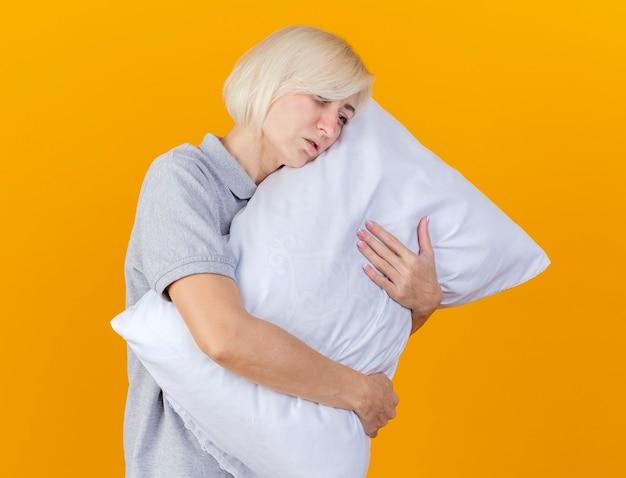Blada młoda blondynka chora kobieta przytula poduszkę patrząc z boku na białym tle na pomarańczowej ścianie