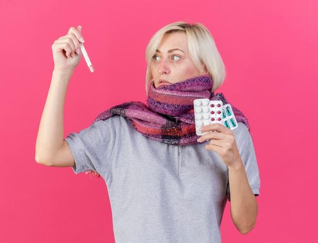 Blada młoda blondynka chora słowiańska kobieta nosi szalik trzyma opakowania tabletek medycznych