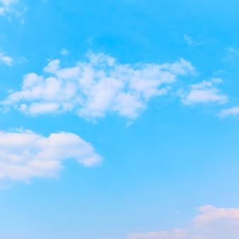 Bladoniebieskie niebo z białymi chmurami - tło z miejscem na własny tekst