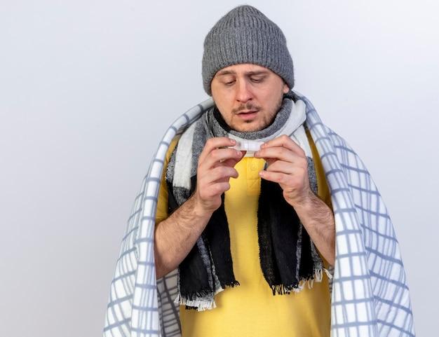 Blady młody blond chory słowiański mężczyzna w czapce zimowej i szaliku owiniętym w kratę trzyma i patrzy na plaster medyczny odizolowany na białej ścianie z miejscem na kopię
